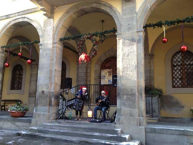 Clima de natal: neve, um casal que canta música ao vivo, barraquinhas e decoração natalina