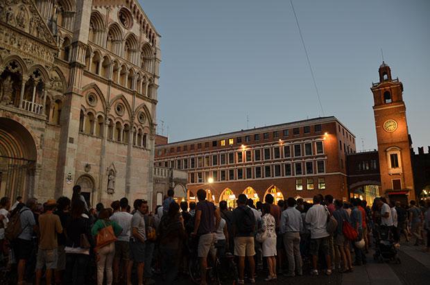 O sol se põe e as pessoas se reúnem para assistir os artistas de rua