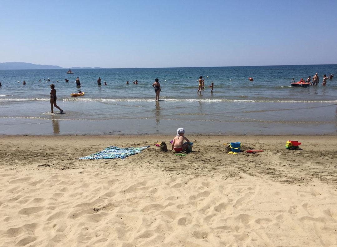 no centro: Gaia brincando na areia